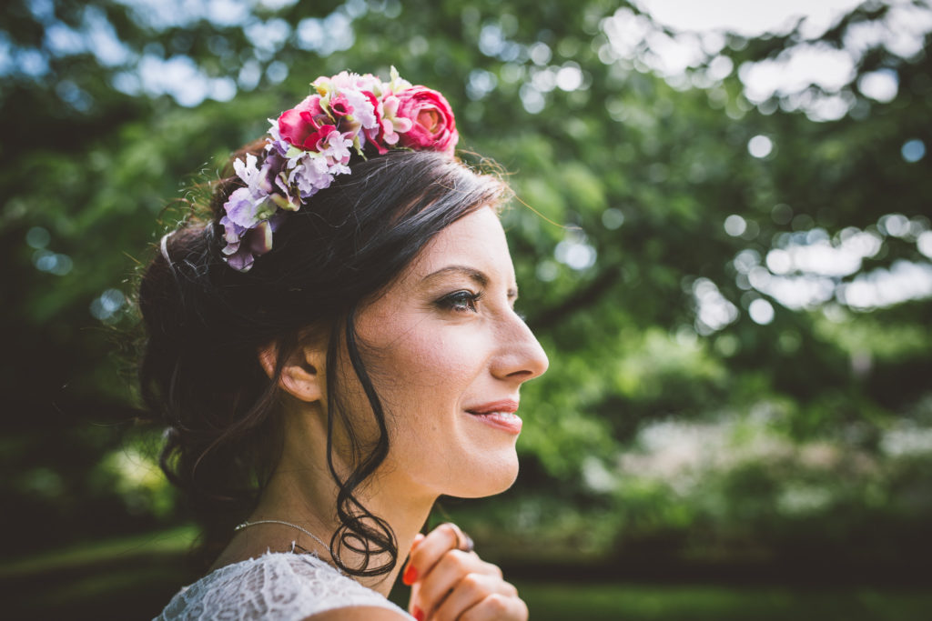 Dark haired woman with flower crown against a leafy background