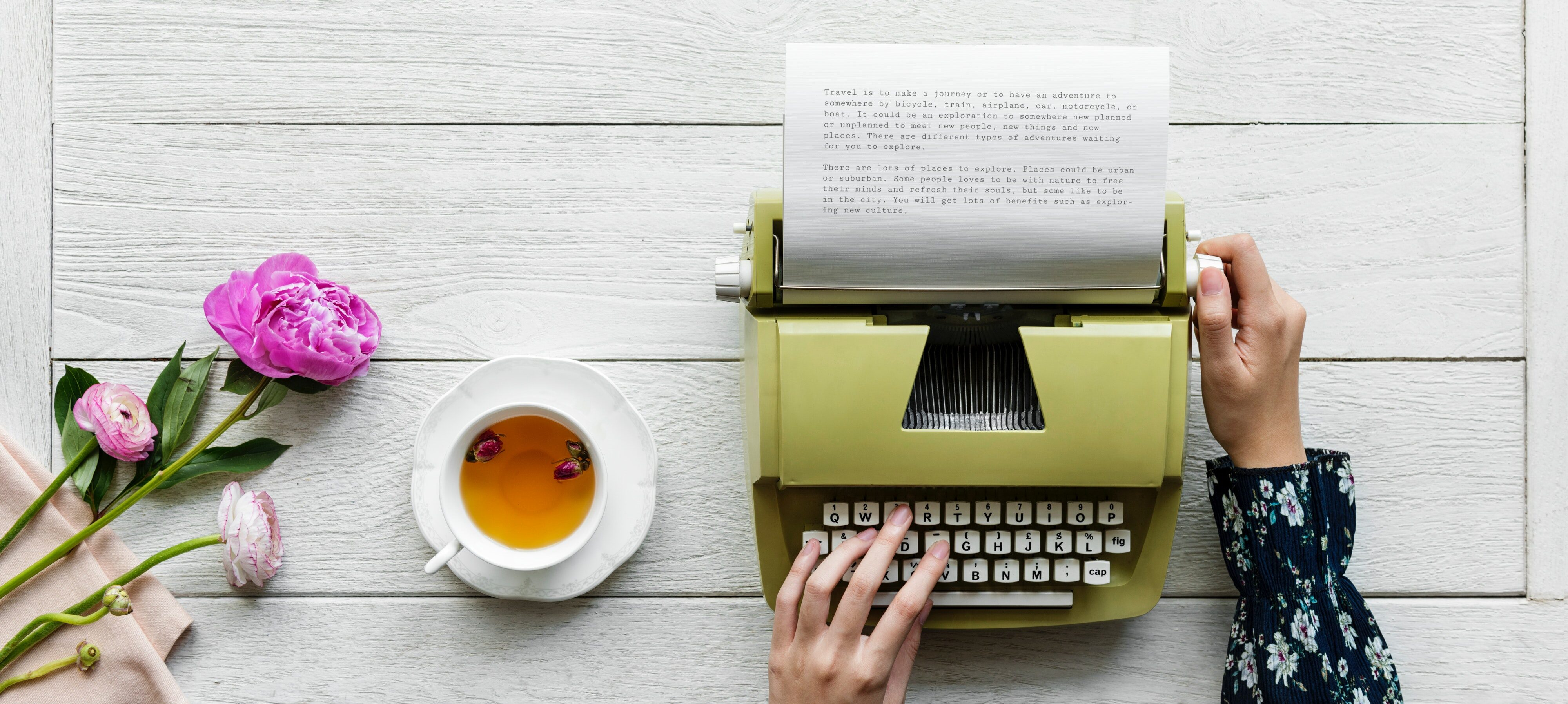Flowers, a cup of herbal tea and hands on a green typewriter against a white background