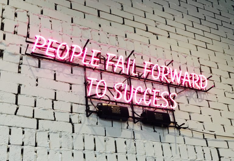 Neon sign against white brick walk saying People Fail Forward To Success