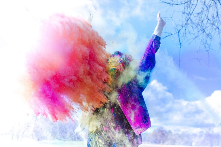 Woman with arms held high as coloured powders burst around her