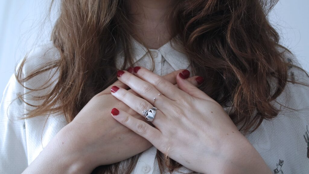 Woman in white shirt with her hands crossed over her heart